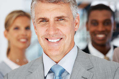 Buy stock photo Closeup portrait of a happy mature businessman with colleagues at the background
