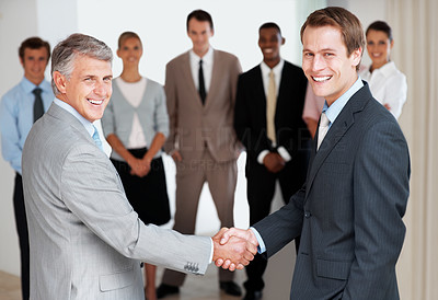 Buy stock photo Portrait of successful business people shaking hands after a deal with team standing in background
