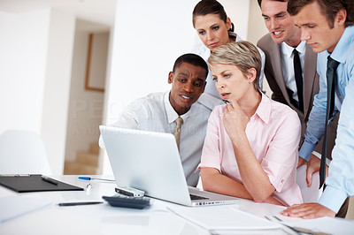 Buy stock photo Portrait of a confident young business group working together on laptop at a meeting