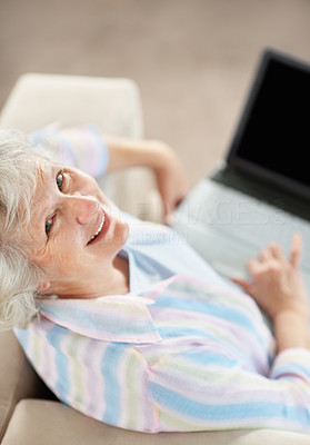 Buy stock photo Portrait of a senior woman working on her laptop while sitting on the sofa at home