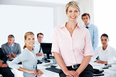 Buy stock photo Successful young businesswoman standing in office with colleagues in the background