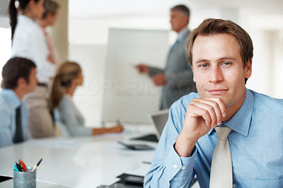 Buy stock photo Closeup portrait of a smart young businessman smiling and his colleagues working in the background