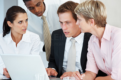 Buy stock photo Group of young executives meeting around a table with laptop