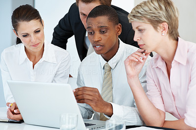 Buy stock photo Male executive viewing proposal on laptop to his colleagues at office