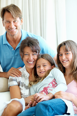 Buy stock photo Family of four sitting together on a sofa and smiling