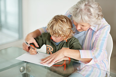 Buy stock photo A senior woman helping her grandson with his homework