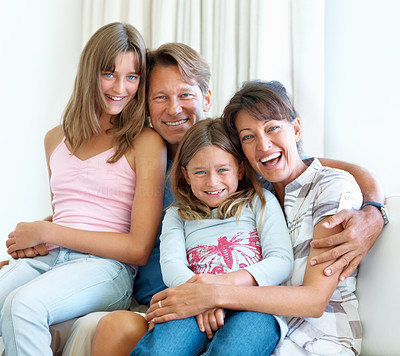 Buy stock photo Happy family of four sitting together on a sofa and smiling