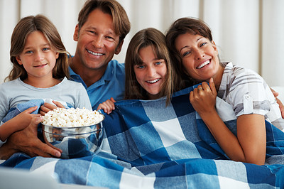 Buy stock photo Portrait of smiling family sitting on sofa watching a movie with popcorn and bed sheet