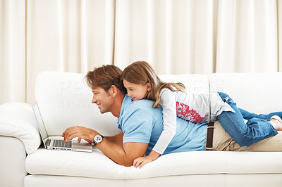 Buy stock photo Father lying on a sofa using laptop with daughter on top of him