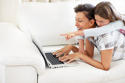 Buy stock photo Mother lying on a sofa using laptop with daughter on top of her pointing at the screen