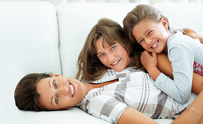 Buy stock photo Mother lying on a sofa with daughters lying on top of her