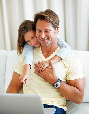 Buy stock photo Man sitting on a sofa using laptop with young daughter pointing at the screen