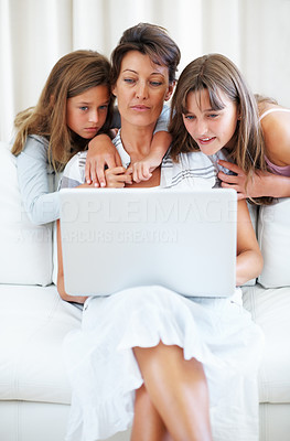 Buy stock photo Mother sitting on a sofa using laptop with children watching from behind