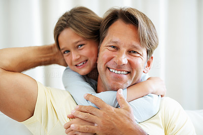 Buy stock photo Closeup portrait of man sitting on a sofa with daughter hugging him from behind