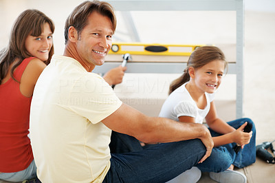 Buy stock photo Portrait of man and his daughters smiling while building a shelf