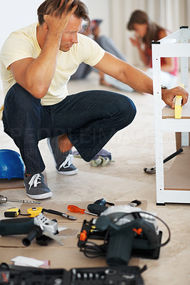 Buy stock photo Man measuring the angle of wooden board while building a shelf and sitting with hand on head in despair