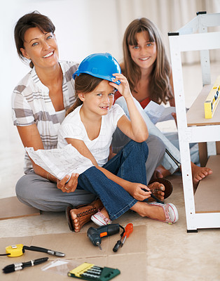 Buy stock photo Portrait of a happy family sitting together while building a shelf