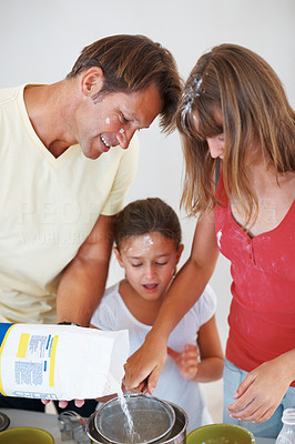 Buy stock photo Father and his two daughters preparing food in the kitchen with father adding flour in a utensil