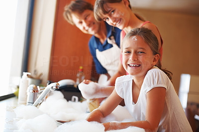 Buy stock photo Portrait of young girl smiling while washing dishes with father and sister in background