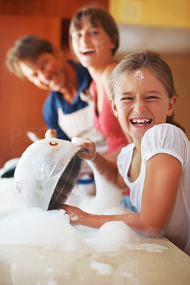 Buy stock photo Portrait of young girl having fun while washing dishes with her sister and father