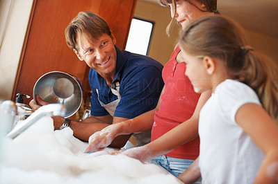 Buy stock photo Family washing dishes with father showing a clean utensil to his daughters