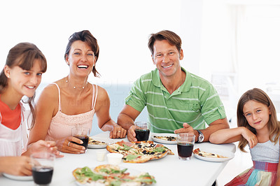Buy stock photo Portrait of happy family sitting at table and having pizza for breakfast