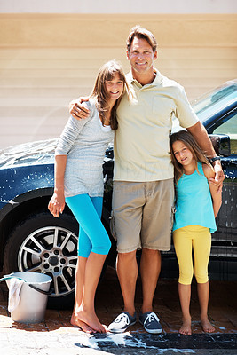 Buy stock photo Full length of man and his two daughters standing together and smiling while washing car on a sunny afternoon