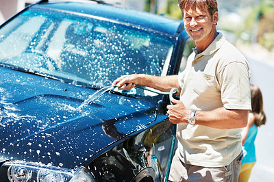 Buy stock photo Portrait of man washing his car and smiling with daughter in background