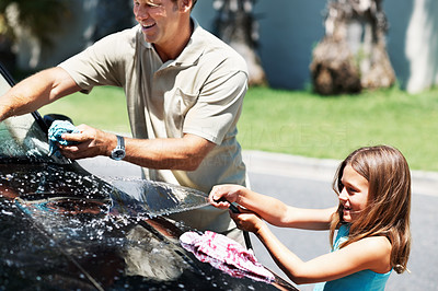 Buy stock photo Man washing his car with his daughter washing their car over the weekend - copyspace