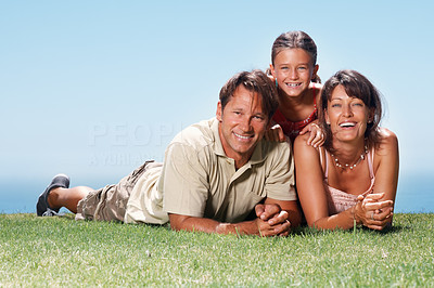 Buy stock photo Family of three lying on the grass and smiling