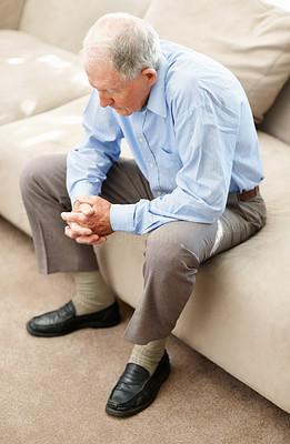 Buy stock photo A sad senior man sitting on the sofa at home