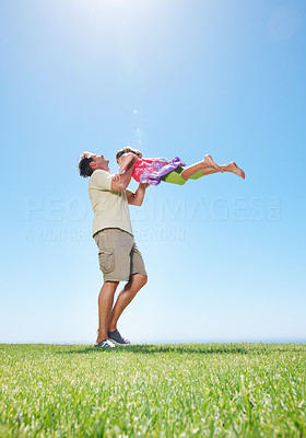Buy stock photo Full length of man standing on grass and lifting his daughter - copyspace