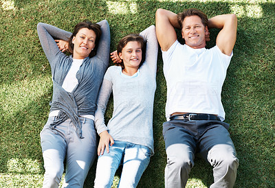 Buy stock photo Top view of happy family relaxing on grass and smiling