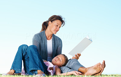 Buy stock photo Woman sitting on grass and reading book with daughter lying on her lap - copyspace