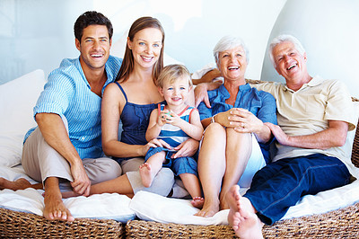 Buy stock photo Smiling family sitting together on a sofa and looking away
