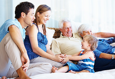 Buy stock photo Cute family sitting on a sofa with young kid holding mother's hands and smiling