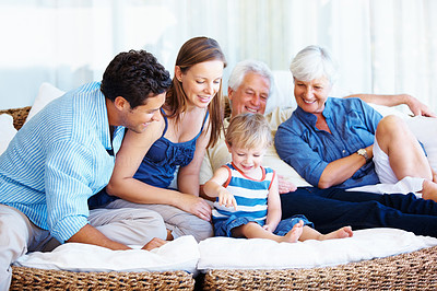 Buy stock photo Attractive family sitting together on a sofa and smiling