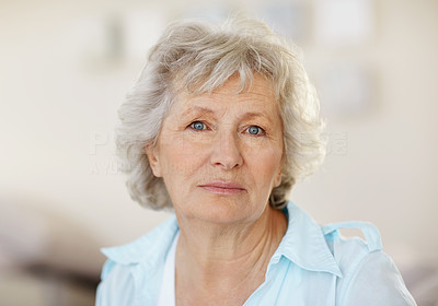 Buy stock photo Closeup portrait of a senior woman looking sad against a blurred background