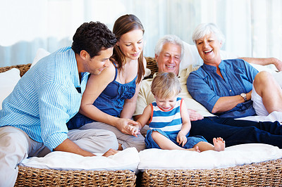Buy stock photo Happy family sitting together on a sofa and smiling