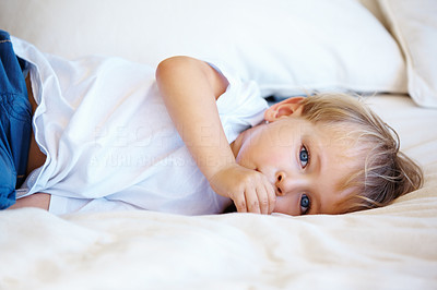 Buy stock photo Portrait of young kid lying on a bed with thumb in mouth