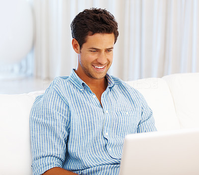 Buy stock photo Smart man sitting on a sofa and having fun on the internet