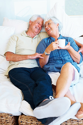 Buy stock photo Smiling senior couple sitting together on a sofa and looking at each other