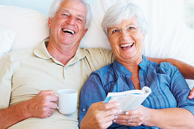 Buy stock photo Portrait of senior couple smiling with man holding a cup and woman holding a book