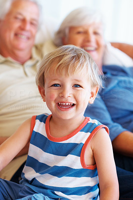 Buy stock photo Portrait of young kid sitting on sofa with grandparents and smiling