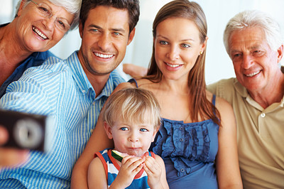Buy stock photo Family sitting together with man holding mobile phone and showing them images