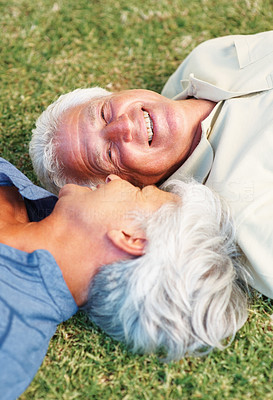 Buy stock photo Closeup of senior couple smiling and looking at each other while lying on grass