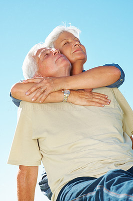 Buy stock photo Senior couple enjoying the tranquil weather with woman embracing man from behind