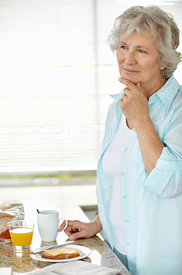Buy stock photo A senior woman looking thoughtful with her hand on her chin while having breakfast