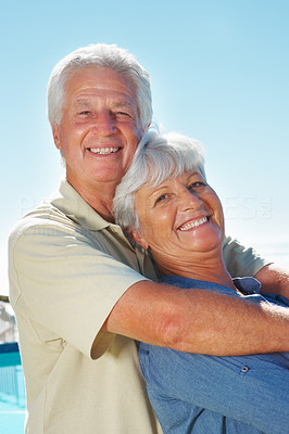 Buy stock photo Portrait of senior couple giving you a warm smile with man embracing woman from behind