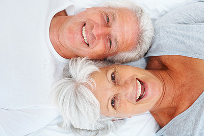 Buy stock photo Closeup portrait of cheerful senior couple lying on bed and smiling